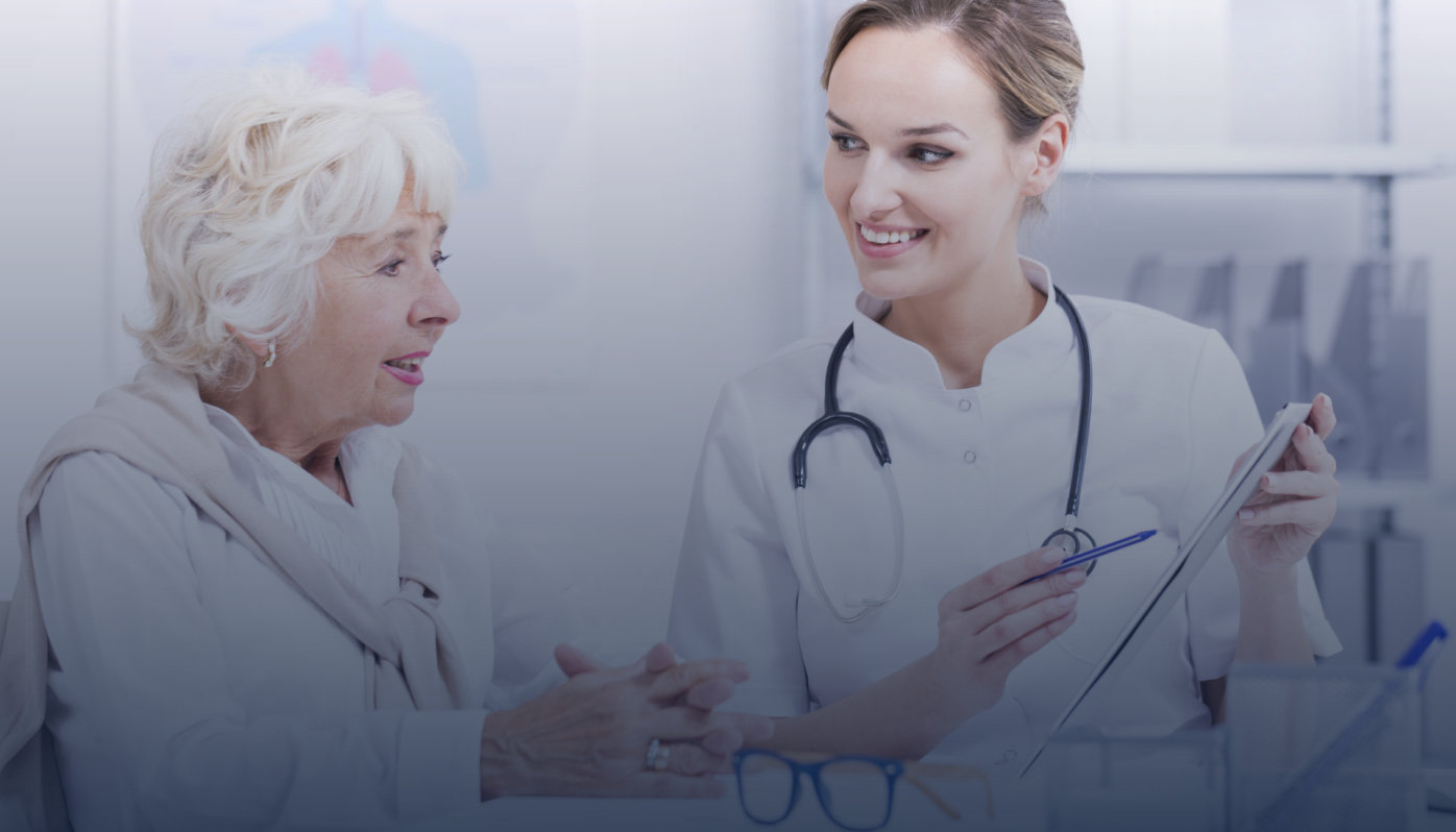 Smiled doctor with the stethoscope talking with the senior woman