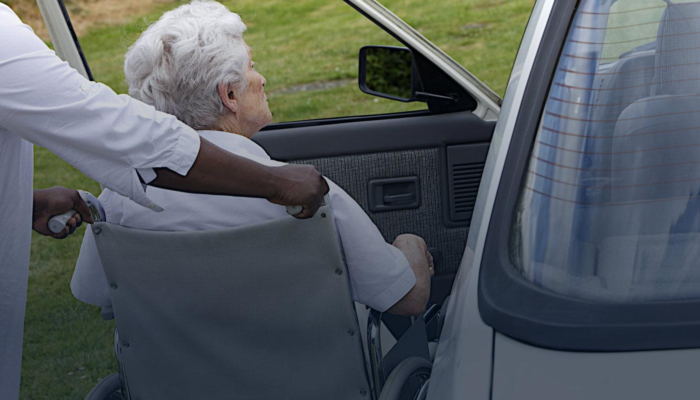 caregiver giving food to a senior man