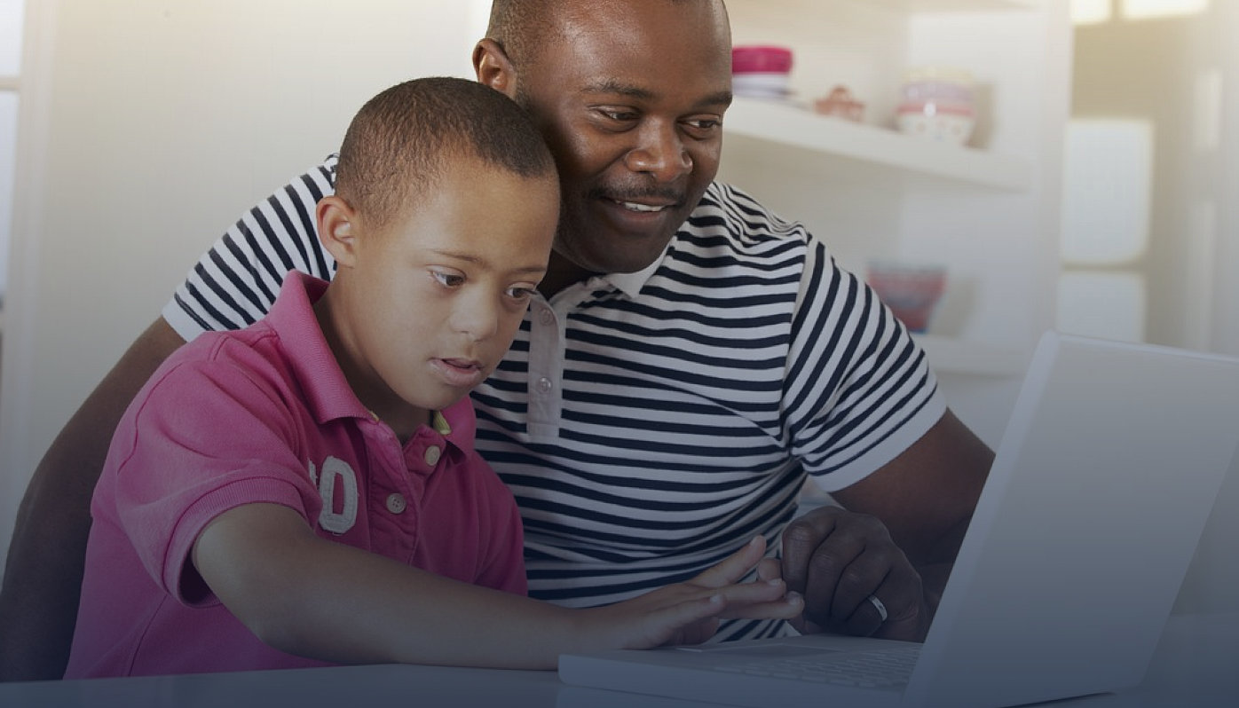 a father using laptop with his son